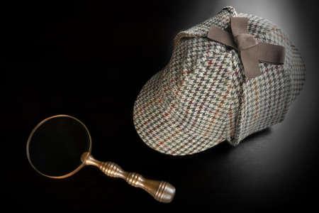 Sherlock Holmes Deerstalker Hat And Vintage  Magnifying Glass On The Black Wooden Table Background. Overhead View.  Investigation Concept.
