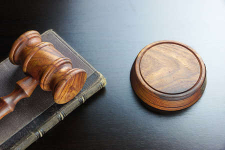 back light: Judges  Or Auctioneers Walnut Gavel And Old Law Book  On The Black Wooden Table Background In The Back Light. Overhead View. Lawsuit or Auction Bidding Concept