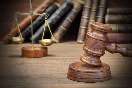 Zbliżenie Z Jydjes Gavel Kodeksu Prawnego, skale Sprawiedliwości na wzburzonych drewniane tle. prawo Concept Zdjęcie Seryjne