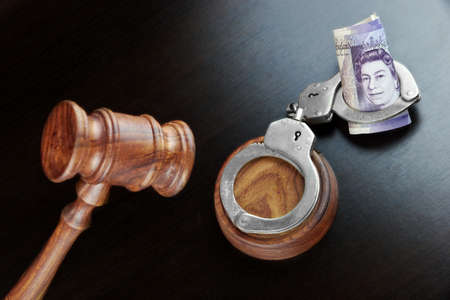 bribing: Concept For Corruption, Bankruptcy, Bail, Crime, Bribing, Fraud. Judges Gavel, Handcuffs   And British Pound Cash On The Rough Black Wooden Textured Table Background. Stock Photo