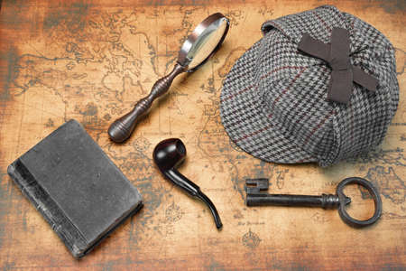 오래된 세계지도 배경에 셜록 홈즈 사슴 사냥꾼 모자와 사립 탐정 도구의 오버 헤드보기. 항목 빈티지 돋보기, 레트로 키, 손으로 책이나 메모장을 포