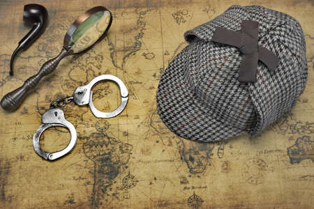 old items: Overhead View Of Sherlock Holmes Deerstalker Hat  And Private Detective Tools On The Old World Map Background. Items Include Vintage Magnifying Glass,  Smoking Pipe And Handcuffs