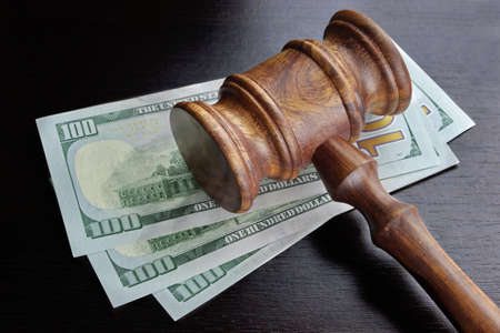 fraud: Concept For Corruption, Bankruptcy, Bail, Crime, Bribing, Fraud, Auction Bidding. Judges or Auctioneer Gavel, Soundboard And Bundle Of Dollar Cash On The Rough Black Wooden Textured Table Background.