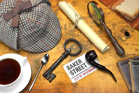 sherlock: Private Investigation Concept. Sherlock Holmes Deerstalker Cap, Full Teacup, Sign BAKER STREET, Roll Of Paper, Vintage Magnifier, Retro Key, Shabby Books and  Notes On The Old Map Background. Top View.