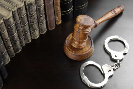 back light: Judges Gavel, Handcuffs And Old Law Book  On The Black Wooden Table Background In The Back Light. Overhead View. Lawsuit or Bail Or Arrest Concept