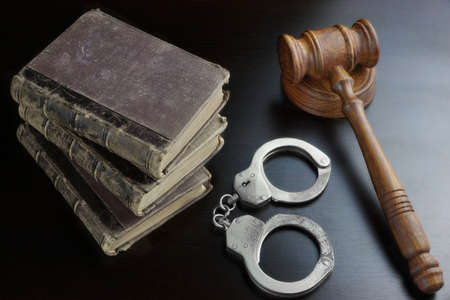 bail: Judges Gavel, Handcuffs And Old Law Book  On The Black Wooden Table Background In The Back Light. Overhead View. Lawsuit or Bail Or Arrest Concept