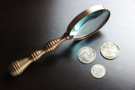 numismatic: Vintage Magnifying Glass And Old Silver Coins On The Black Wood Table  In Back Light. Overhead View. Numismatic Concept
