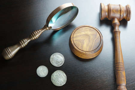 numismatic: Auctioneers Or Judges Gavel And Old Coins On Black Table In The Back Light. Overhead View.  Numismatic  Collection Or Auction Concept