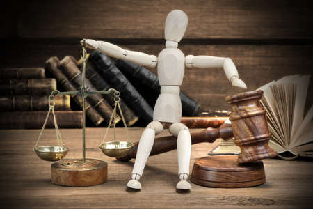wood figurine: Wooden Figurine With Judges Gavel And Scale Of Justice And Old Law Book On The Rough Wood Table Background