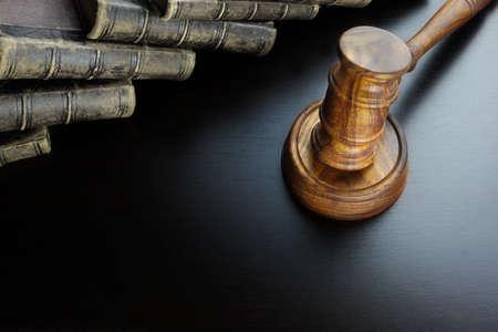 Richter oder Auktionatoren Walnut Hammer und alte Gesetzbuch auf der schwarzen Holztisch Hintergrund im Gegenlicht. Draufsicht. Strafanzeige oder Auktion Gebotskonzept