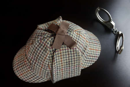 cuffs: Sherlock Holmes Deerstalker Hat And Cuffs On The Black Wooden Table Background In The Back Light