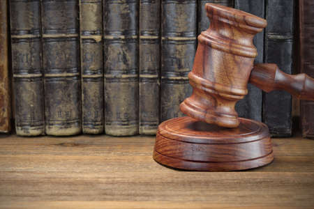 auctioneer: Wooden Judges Or Auctioneer Gavel And Old Law Books On The Rough Wooden Table In The Background. Law Concept. Front View Stock Photo
