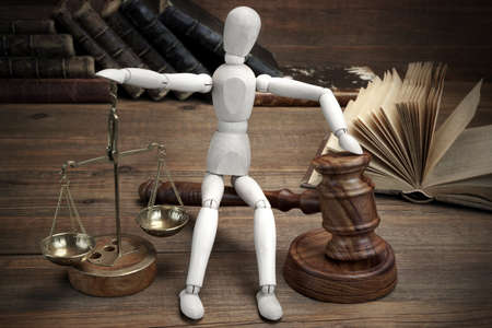 Wooden Figurine With Judges Gavel And Scale Of Justice And Old Law Book On The Rough Wood Table Background