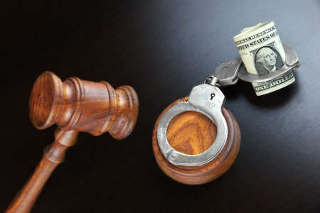 bidding: Concept For Corruption, Bankruptcy, Bail, Crime, Bribing, Fraud, Auction Bidding. Judges or Auctioneer Gavel, Soundboard And Bundle Of Dollar Cash On The Rough Black Wooden Textured Table Background.