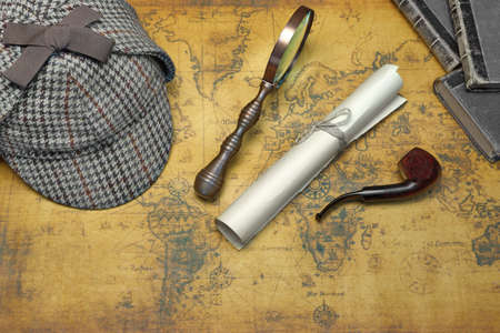sherlock: Overhead View Of Sherlock Holmes Deerstalker Hat  And Private Detective Tools On The Old World Map Background. Items Include Vintage Magnifying Glass, Retro Key, Manuscript, Smoking Pipe