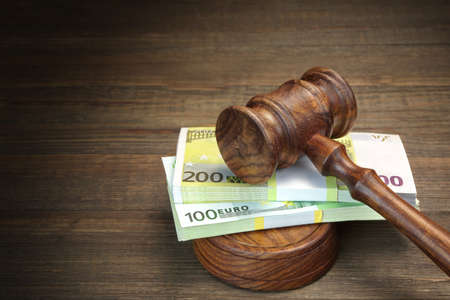 confiscation: Concept For Corruption, Bankruptcy Court, Bail, Crime, Bribing, Fraud, Auction Bidding. Judges or Auctioneer Gavel And Bundle Of Euro Cash On The Rough Wooden Textured Table Background. Top View