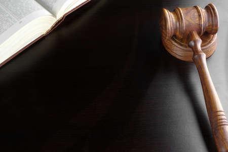 裁判官または競売クルミ小槌と古い法律ライト裏の黒い木製テーブル背景の本。オーバーヘッドのビュー。訴訟や概念を入札オークション