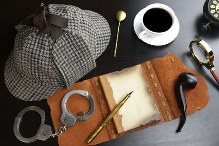 cuffs: Sherlock Holmes Concept. Private Detective Tools On The Black Wood Table Background. Deerstalker Hat, Opened Notebook With Blank Brown Page, Pipe, Magnifying Glass, Cuffs, Fountain Pen Stock Photo