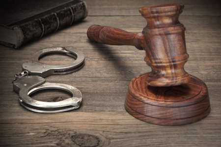 Real Handcuffs, Wooden Judge Gavel And Old Law Books On The Rough Brown Wooden Table Background. Arrest in the Courtroom Concept Or Release From Custody Stock Photo