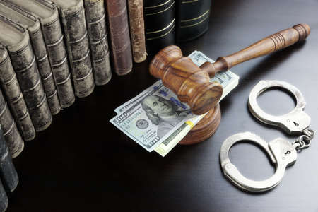 handcuffs: Judges Gavel, Handcuffs, Dollar Cash And Old Law Book  On The Black Wooden Table Background In The Back Light. Overhead View.
