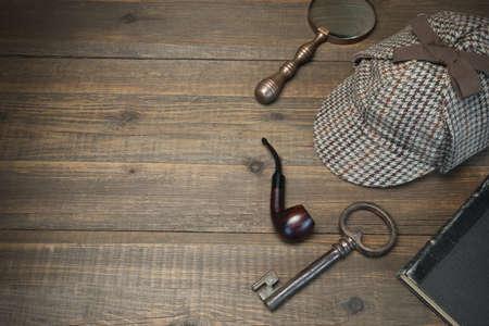 셜록 홈즈 개념입니다. 우드 테이블 배경에 사립 탐정 도구. 사슴 사냥꾼 모자, 올드 키와 도서, 담배 파이프, 빈티지 돋보기