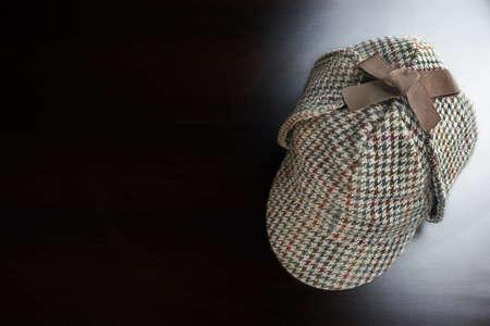 animal private: Sherlock Holmes Deerstalker Hat On The Black Wooden Table Background In The Back Light