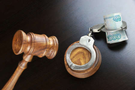 bribing: Concept For Corruption, Bankruptcy, Bail, Crime, Bribing, Fraud. Judges Gavel, Handcuffs   And Russian Cash On The Rough Black Wooden Textured Table Background.