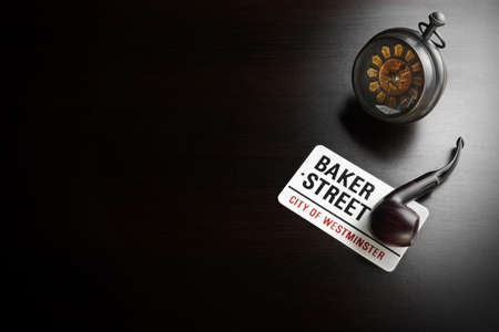 deductive: Baker Street Sign And Sherlock Holmes Symbol On The Black Wood Table In The Back Light. Background With Copy Space Stock Photo