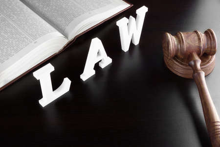 latter: Judges Gavel, Red Open Legal Book And White Sign LAW From Wood Latter On The Black Table In The Back Light. Overhead View. Stock Photo