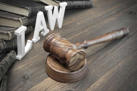 injunction: Concept For Law, Lawsuit, Court, Crime. Judges Gavel, Sign Law Old Law Book On The Rough Wooden Vintage Textured Table Background. Stock Photo