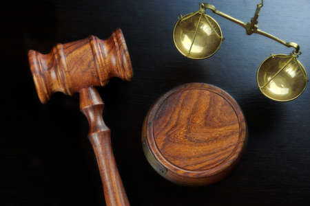 legally: Judges Gavel And Scale Of Justice On The Black Table Background  In Back Light. Overhead View. Law Concept Stock Photo