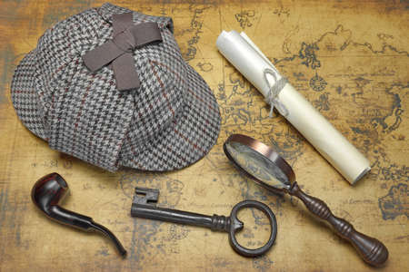 old items: Overhead View Of Sherlock Holmes Deerstalker Hat  And Private Detective Tools On The Old World Map Background. Items Include Vintage Magnifying Glass, Retro Key, Manuscript, Smoking Pipe