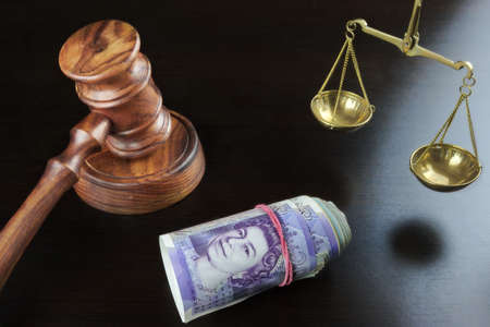 Concept For Corruption, Bankruptcy, Bail, Crime, Bribing, Fraud. Judges Gavel, Scale Of Justice And British Cash On The Rough Black Wooden Textured Table Background. Stock Photo