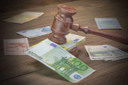 solicitor: Concept For Corruption, Bankruptcy Court, Bail, Crime, Bribing, Fraud, Auction. Judges or Auctioneer Gavel, Bundle Of Euro Cash And Old Law Book  Library On The Rough Wooden Table Background. Stock Photo