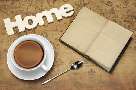 tea house: White Tea Cup, Wooden Sign HOME And Vintage Notebook With Blank Brown Page On The Old World Map Background. Overhead View. Travel Or Adventure Or Dream Concept With Arrangement On The Old Map. Stock Photo