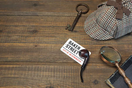 Sherlock Holmes Concept. Private Detective Tools On The Wood Table Background. Deerstalker Cap, Old Key  And Book, Tobacco  Pipe, Vintage   Magnifying Glass Stock Photo