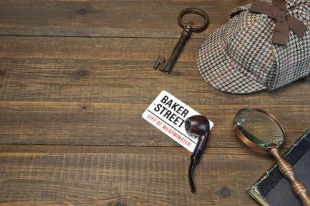 Sherlock Holmes Concepto. Herramientas de detectives privados sobre el fondo de la mesa de madera. Deerstalker Cap, Clave y libro viejos, tabaco de pipa, Vintage Lupa Foto de archivo - 51563327