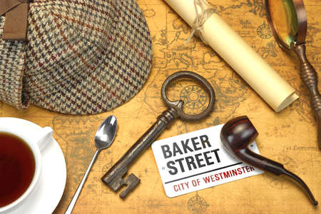 Private Investigation Concept. Sherlock Holmes Deerstalker Cap, Full Teacup, Sign BAKER STREET, Roll Of Paper, Vintage Magnifier, Retro Key, Shabby Books and  Notes On The Old Map Background. Top View.