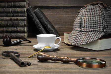 Sherlock Holmes Concept. Privé-detective Hulpmiddelen Op de houten tafel Achtergrond. Deerstalker Cap, Magnifier, Key, Cup, Notebook, pijp roken. Stockfoto
