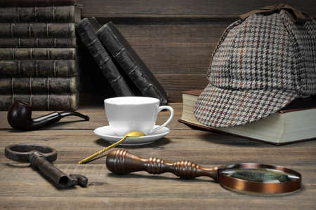 Sherlock Holmes Concept. Private Detective Tools On The Wood Table Background. Deerstalker Cap,  Magnifier, Key, Cup, Notebook, Smoking Pipe. Фото со стока