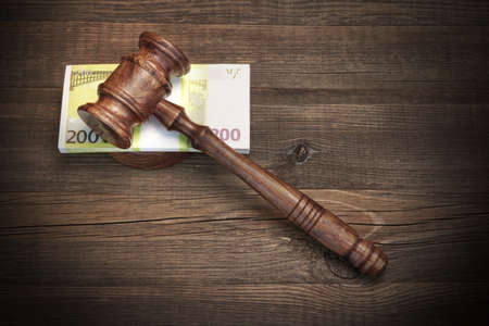 forfeiture: Concept For Corruption, Bankruptcy Court, Bail, Crime, Bribing, Fraud, Auction Bidding. Judges or Auctioneer Gavel And Bundle Of Euro Cash On The Rough Wooden Textured Table Background. Top View