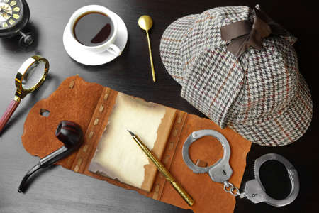 private detective: Sherlock Holmes Concept. Private Detective Tools On The Black Wood Table Background. Deerstalker Hat, Opened Notebook With Blank Brown Page, Pipe, Magnifying Glass, Cuffs, Fountain Pen Stock Photo