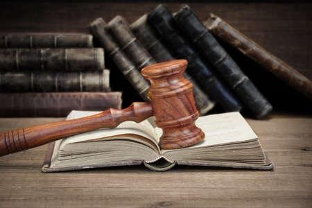libros abiertos: Los jueces de madera o subastador Gavel y abrir ley viejos libros sobre la mesa de madera áspera en el fondo. Concepto de la ley. Vista de frente, Close Up