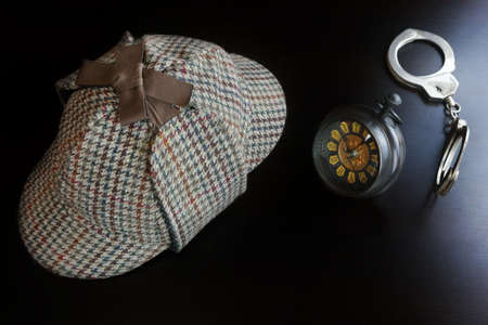cuffs: Sherlock Holmes Deerstalker Hat, Hand Cuffs, Vintage Retro Clock On The Black Wooden Table Background In The Back Light