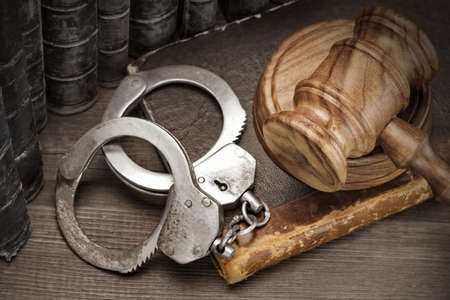 cuff bracelet: Real Handcuffs, Wooden Judge Gavel And Old Law Books On The Rough Brown Wooden Table Background. Arrest in the Courtroom Concept Or Release From Custody Stock Photo