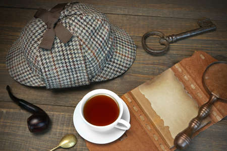 private detective: Sherlock Holmes Concept. Private Detective Tools On The Wood Table Background. Deerstalker Cap,  Magnifier, Key, Cup, Notebook, Smoking Pipe. Stock Photo