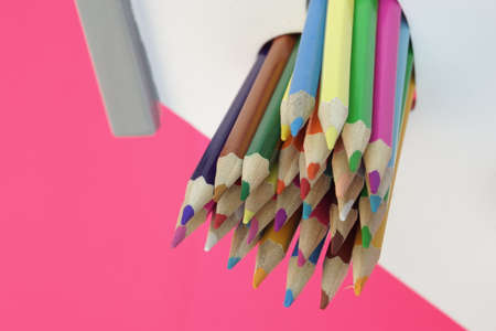 stripe background: A Lot Of Sharped Colored Pencils Are Sticking Out From The Heart Shaped Window In The Home White Wall Isolated On Pink Background, Vertical Image Stock Photo