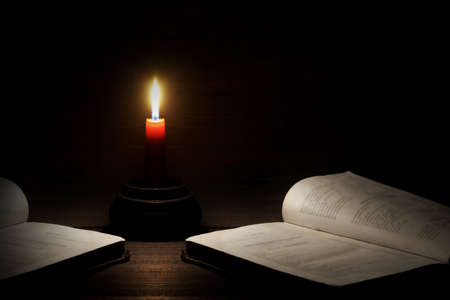 lighted: Lighted Candle And Two Open Books On The Rough Wood Horizontal Background With Copy Space