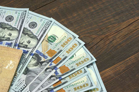 dollars: American One Hundred Dollar Bills In The  Notepad Top View On The Rough Wooden Table Background With Copy Space