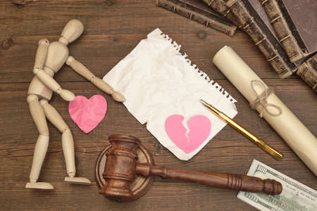broken contract: Divorce Concept In The Court. Gavel, Law Book, Judges Gavel, Empty White Page, Broken Paper Heart On Wood Background